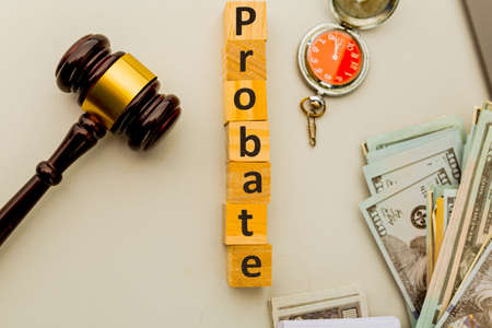 Probate word on the wooden little cubes and gavel on the table. Фото со стока