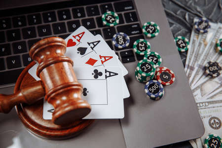 Judge wooden gavel, money banknotes and playing cards on computer keyboard, legal rules for online gambling concept