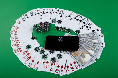 Smartphone and poker chips with playing cards and money banknotes on a green table. Online casino concept. 版權商用圖片