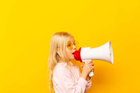 Kid shouting through megaphone. Communication concept. yellow background as copy space for your text