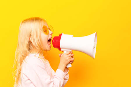 Kid shouting through vintage megaphone. Communication concept. Blue sky background as copy space for your text