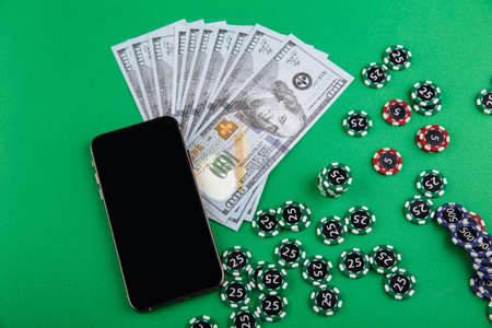 Online casino smartphone with poker chips device and money over green table Stock Photo