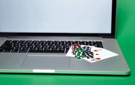 Stacks of poker chips and playing cards on a laptop computer. Online casino concept 写真素材 - 152214547