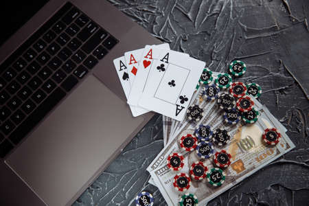 Stacks of poker chips, money banknotes and playing cards on a laptop computer. Online casino concept Stockfoto