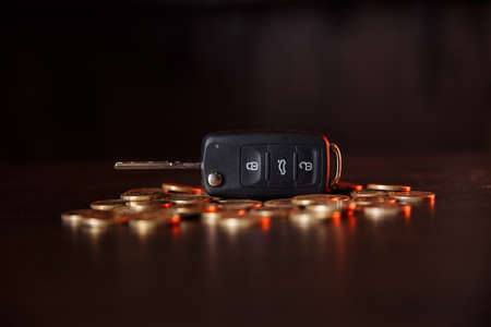 Car key with coins on wooden table. Concept of the saving money for car, trade car for cash