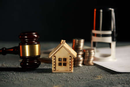 Miniature house with money and tax papers