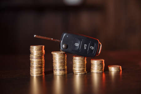 Stack of coins with black car key placed on desk Banque d'images
