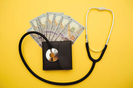 Wallet with stethoscope isolated on yellow