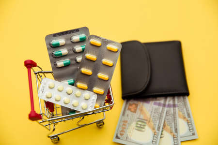 Grey wallet with money and trolley with tablets of pills on yellow background