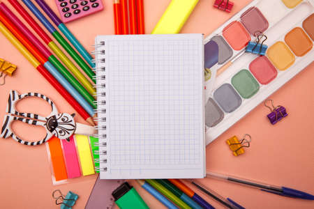 School notebook and various stationery on pink background. Back to school concept.