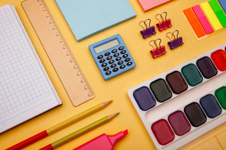 School supplies on yellow background. Back to school abstract background. Creative flat lay