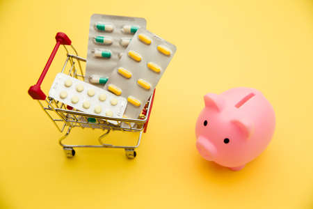 Piggy bank and trolley of pills on yellow background. Medicine bills