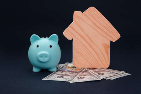 Blue piggy bank with model of house and money banknotes on blue background. Savings money for buy house
