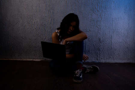 sad and scared female teenager with computer laptop suffering cyberbullying and harassment being online feeling desperate and humiliated in cyber bullying