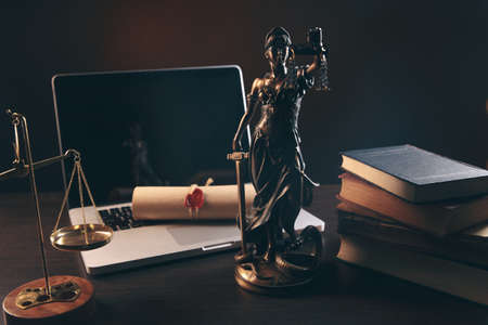Statue of Justice with scales and lawyer working on a laptop. Legal law, advice and justice concept