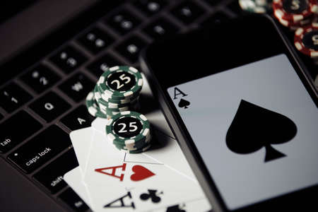 Close-up poker chips, playing cards and smartphone on keyboard