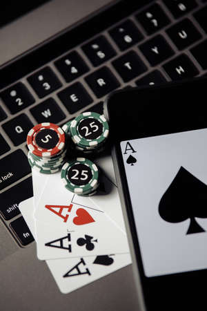Gambling chips, smartphone and playing cards on keyboard close-up Reklamní fotografie
