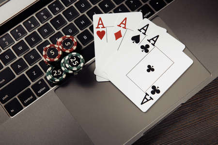 Stack of gambling chips and playing cards on keyboard.