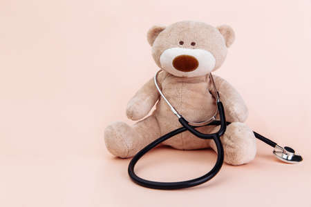 Stuffed Bear animal presented as a pediatrician holding a stethoscope with copy space