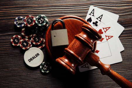 Judges wooden gavel, poker chips and playing cards on wooden background. Concept of Law and regulation of gambling.