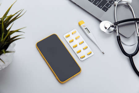 Medical desktop with stethoscope, pills, thermometer, smartphone and laptop