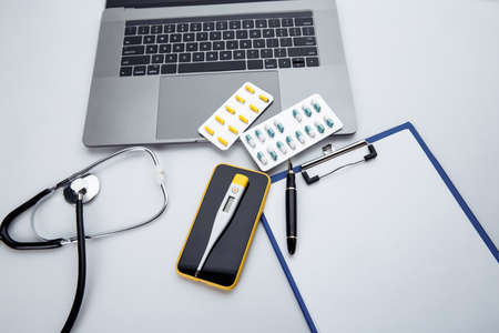 Medical desktop with stethoscope, pills, thermometer, smartphone and laptop keyboard