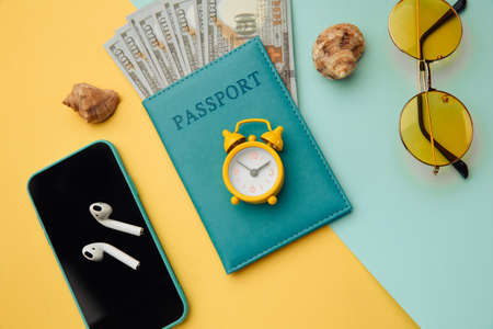 Outfit and accessories of traveler on yellow blue background. Overhead view of travelers accessories 스톡 콘텐츠
