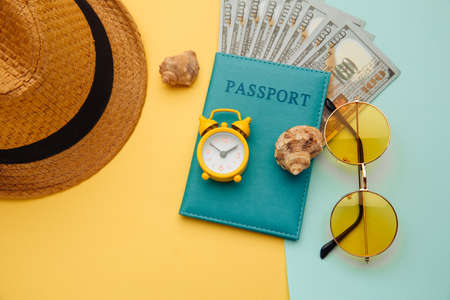 Vacation concept. Minimal simple flat lay with passport, sunglasses, hat and shell on yellow blue background. Tourist essentials