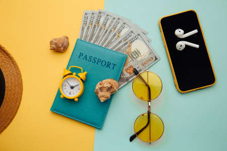 Summer vacation concept. Sunglasses, smartphone, hat and passport with money banknotes on blue yellow background 스톡 콘텐츠
