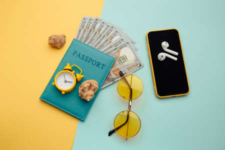 Summer vacation composition. Sunglasses, smartphone, shell and passport with money banknotes