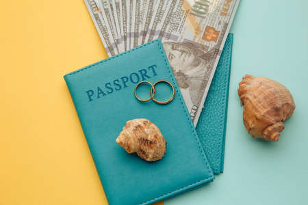 Honeymoon traveling concept. Passports with money and shells on a colored background 스톡 콘텐츠