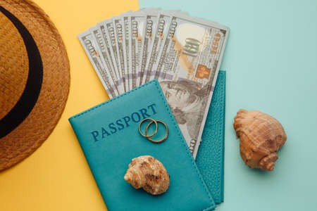 Honeymoon traveling concept. Passports with money, tourist hat and shells on a blue yellow background 스톡 콘텐츠