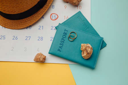Calendar with passports, hat and rings on colorful background. Honeymoon, wedding concept