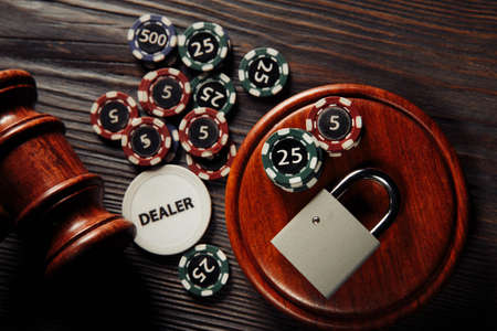 Law and rules for online gambling concept, judge gavel with padlock and aces on wooden background 스톡 콘텐츠