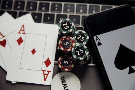 Online poker casino theme. Close-up gambling chips, smartphone and playing cards on keyboard