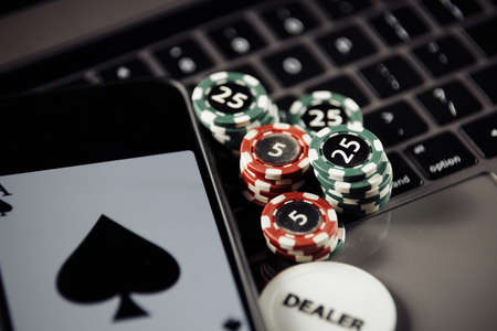 Poker play online concept. Poker chips, playing cards and smartphone on keyboard