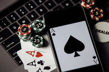 Stack of gambling chips, smartphone and playing cards on a laptop keaboard. Close-up. Online casino concept 스톡 콘텐츠