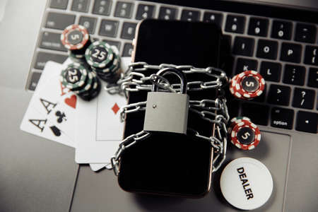 Law and rules for online casino concept, smartphone with padlock and playing chips on keyboard