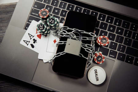 Law and rules for online gambling concept, smartphone with padlock and playng cards on laptop