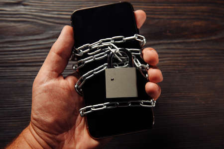 Mans hand holding a smartphone with padlock. Concept of smartphone protection against malware, antivirus