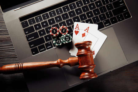 Wooden gavel, playing chips and cards on laptop keyboard. Concept of Law and regulation of gambling