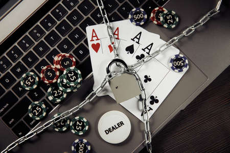 Padlock, playing chips and cards on keyboard. Concept of Law and Regulation of gambling
