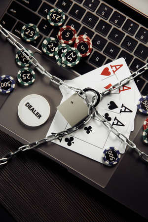 Padlock, playing chips and cards on laptop keyboard. Concept of Law and regulation of gambling