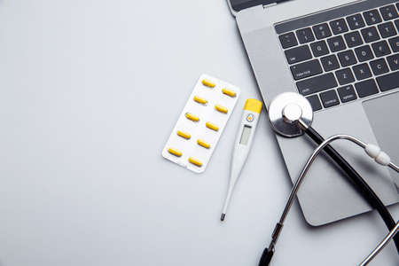 White doctor desk with pills and thermometer with copy space. Professional concept 스톡 콘텐츠
