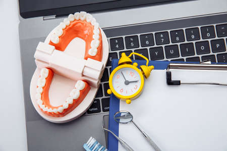 Healthy tooth model with dental tool and alarm clock in dentists office. Time for professional teeth hygiene