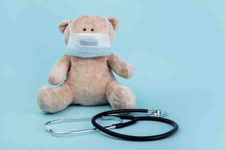 Stuffed Bear animal in mask with stethoscope isolated on blue. Children healthcare concept