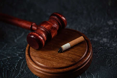 Judge gavel and broken cigarette on grey table. Tobacco law