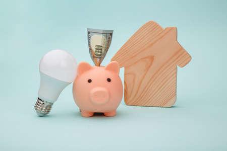 Piggy bank and led light bulb, house figure on blue background. Energy saving concept 스톡 콘텐츠