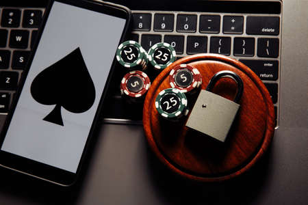 Smartphone and padlock, poker chips and playing cards on laptop keyboard. Concept of Law and regulation of gambling