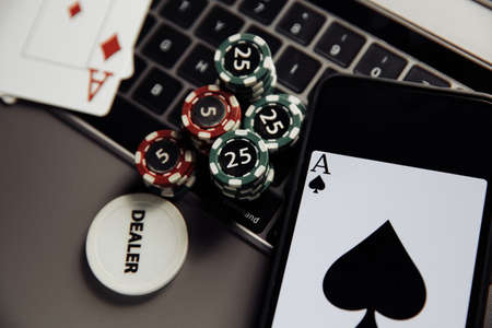Poker play online. Poker chips, playing cards and smartphone on keyboard